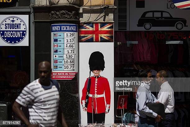 A pedestrian walks past a souvenir shop displaying a photograph of Beefeater standing on duty outside the store on Piccadilly Circus in London UK on...