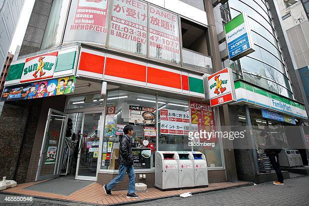 A pedestrian walks past a Sunkus convenience store operated by Circle K Sunkus Co a subsidiary of Uny Group Holdings Co left while another stands in...