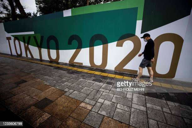 Pedestrian walks past a Tokyo 2020 Olympic and Paralympic Games decoration board on a wall of the Odaiba Marine Park, the venue for marathon swimming...