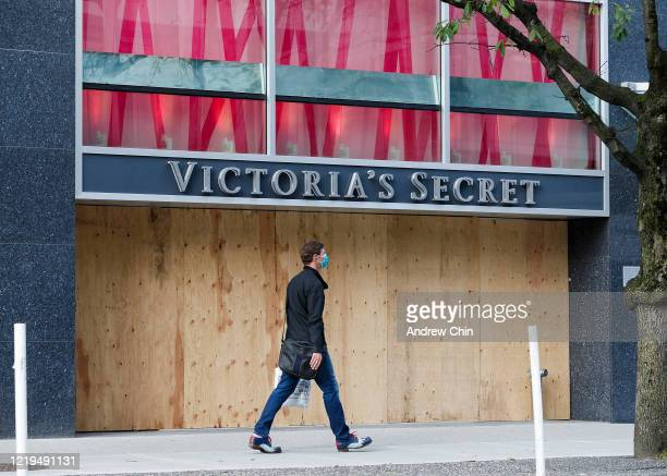 Pedestrian walks past a Victoria's Secret storefront closed and boarded up on Robson Street during the COVID-19 crisis on April 17, 2020 in...