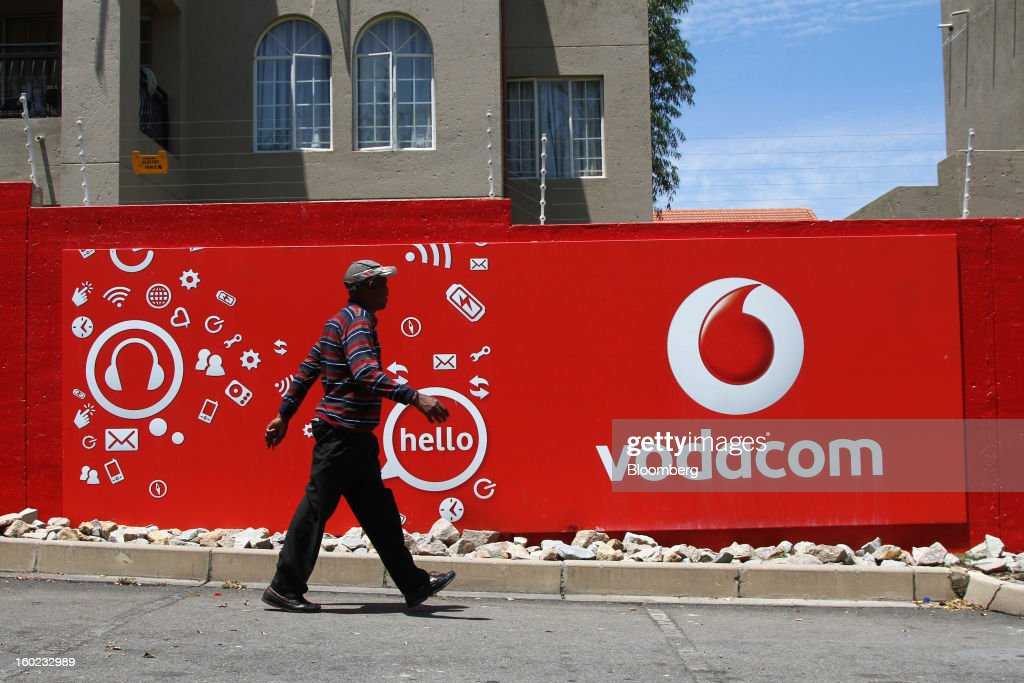 A pedestrian walks past a Vodacom-branded billboard at a taxi rank near Vodaworld, the headquarters of Vodacom Group Ltd., Vodafone's biggest African business, in Johannesburg, South Africa, on Monday, January 28, 2013. Almost two decades after Vodafone Group Plc entered Africa, the region -- where most people earn less than $2 a day and mobile phone towers run on diesel -- is turning into one of the company's biggest profit generators. Photographer: Nadine Hutton/Bloomberg via Getty Images