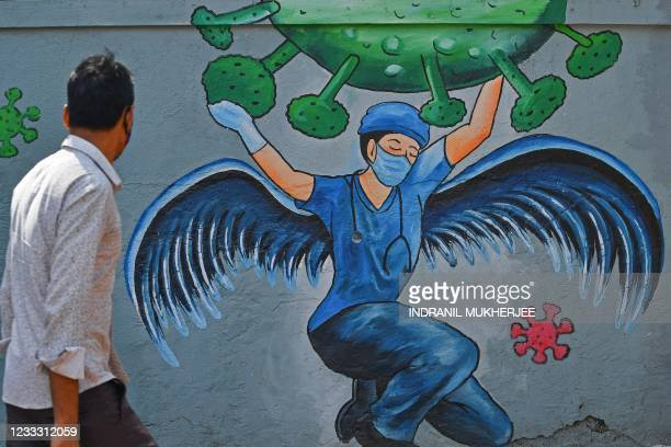 Pedestrian walks past a wall mural representing awareness measures against the Covid-19 coronavirus featuring a frontline medical staff as a guardian...