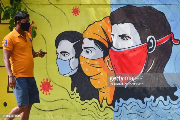 Pedestrian walks past a wall mural representing awareness measures against the Covid-19 coronavirus in Navi Mumbai on June 7, 2021.