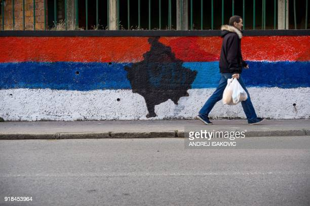 A pedestrian walks past a wall painted in the colours of the Serbian national flag with a map of Kosovo in the middle in Belgrade on February 12 2018...