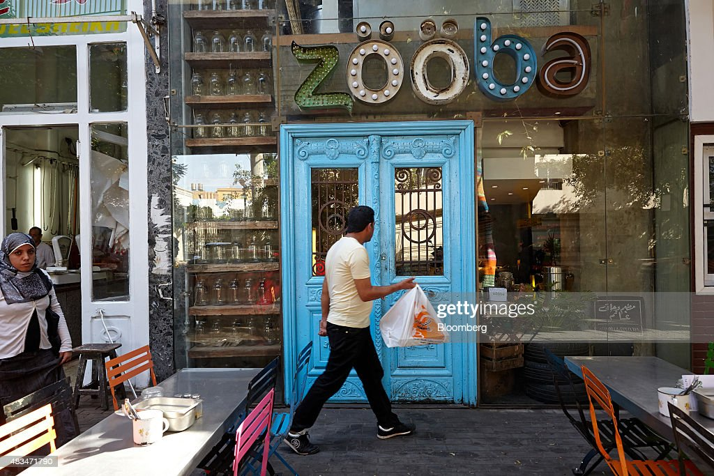 A pedestrian walks past a Zooba restaurant on a street in Cairo, Egypt, on Friday, Aug. 7, 2015. The Suez canal extension and other construction projects have boosted the economy, which grew above 4 percent in the nine months to March for the first time since 2010. Photographer: Shawn Baldwin/Bloomberg via Getty Images