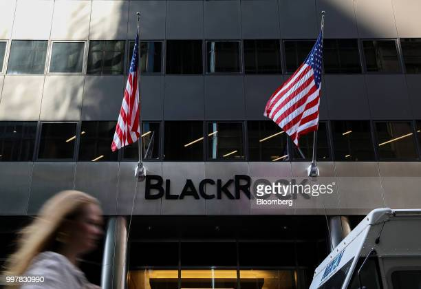 A pedestrian walks past American flags flying at BlackRock Inc headquarters in New York US on Wednesday June 11 2018 BlackRock Inc is scheduled to...