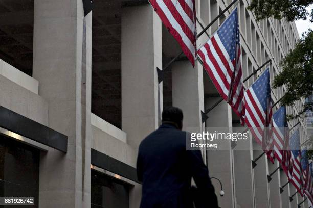 A pedestrian walks past American Flags hanging on display outside the Federal Bureau of Investigation headquarters in Washington DC US on Thursday...