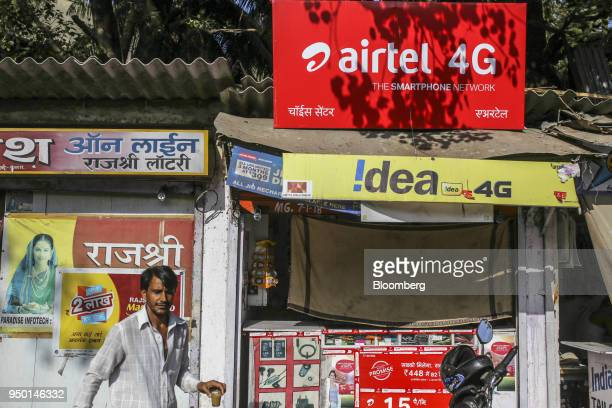 A pedestrian walks past an advertisement for Bharti Airtel Ltd outside a sim card store in Mumbai India on Saturday April 21 2018 Bharti Airtel are...