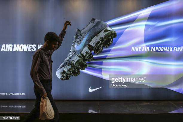 A pedestrian walks past an advertisement for Nike Inc in Mumbai India on Friday Dec 15 2017 India's inflation surged past the central bank's target...