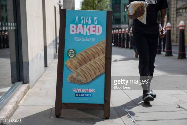 Pedestrian walks past an advertising sign for vegan sausage rolls at a Greggs Plc sandwich chain outlet in London, U.K., on Wednesday, May. 15, 2019....