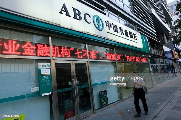 A pedestrian walks past an Agricultural Bank of China Ltd branch in Beijing China on Thursday Aug 23 2012 Chinese lenders are grappling with rising...