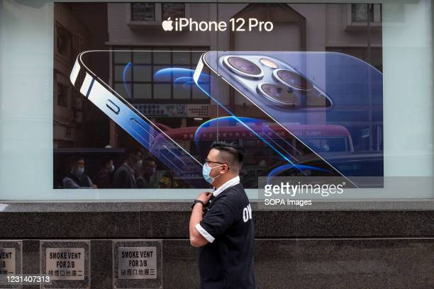 Pedestrian walks past an American multinational technology company, Apple Iphone 12 Pro advertisement in Hong Kong.