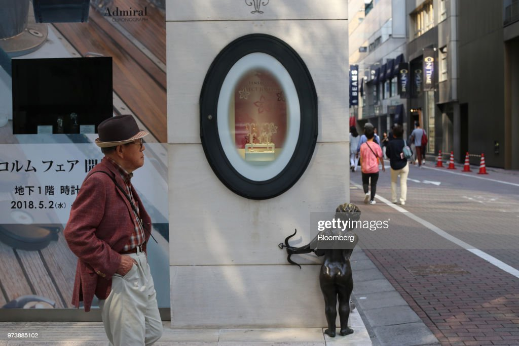 A pedestrian walks past an angel statue at the corner of a building in the Ginza district of Tokyo, Japan, on Sunday, May 28, 2018. The savings-rich elderly spend about 9.7 trillion yen ($87 billion) a year on their offspring and such spending last year accounted for about a third of the modest growth in total consumption, according to Hiromichi Shirakawa, chief Japan economist at Credit Suisse Group. Photographer: Takaaki Iwabu/Bloomberg via Getty Images
