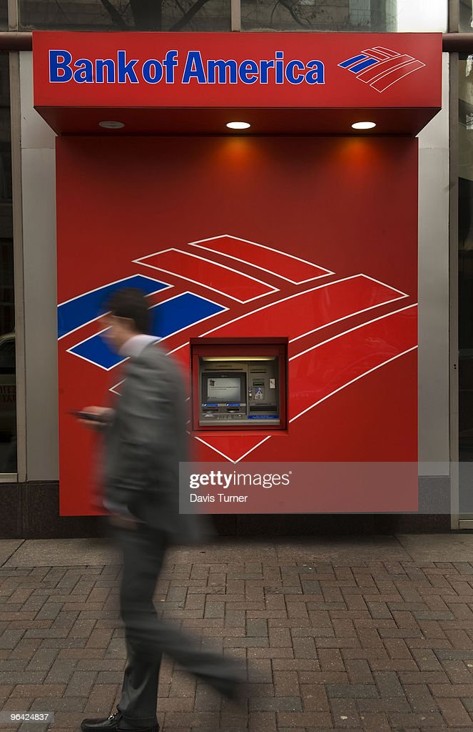 A pedestrian walks past an ATM near the Bank of America headquarters on February 4, 2010 in Charlotte, North Carolina. Bank of America's former Chief Executive Officer Ken Lewis and former Chief Financial Officer Joe Price have been charged with securities fraud by the New York attorney general.