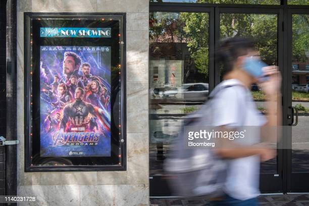 A pedestrian walks past an Avengers Endgame poster in Berkeley California US on Monday April 29 2019 The movie took in $122 billion in its debut...