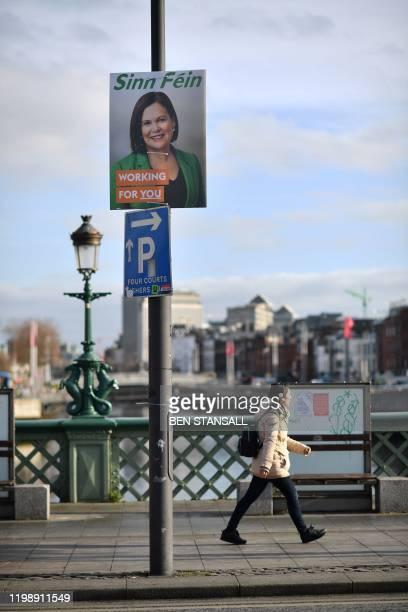 A pedestrian walks past an election poster featuring Sinn Fein President Mary Lou McDonald on Grattan Bridge in Dublin on February 6 ahead of the...