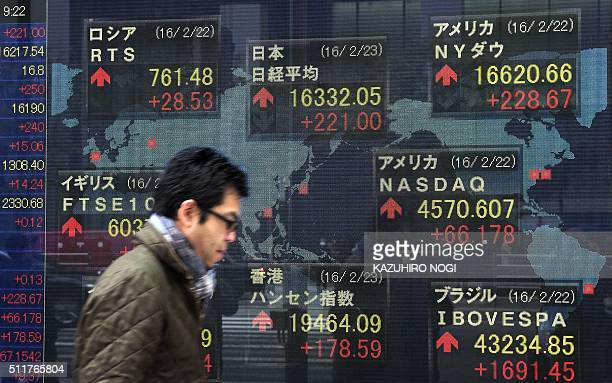 A pedestrian walks past an electric quotation board showing share price indexes of the Tokyo Stock Exchange in front of a securities company in Tokyo...