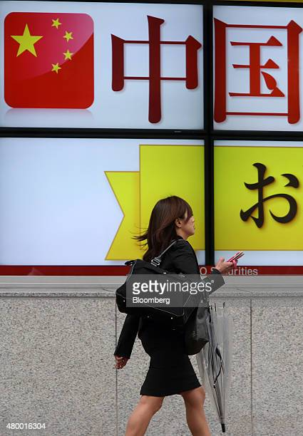 A pedestrian walks past an electronic board displaying an advertisement of Chinese stocks outside a securities firm in Tokyo Japan on Thursday July 9...