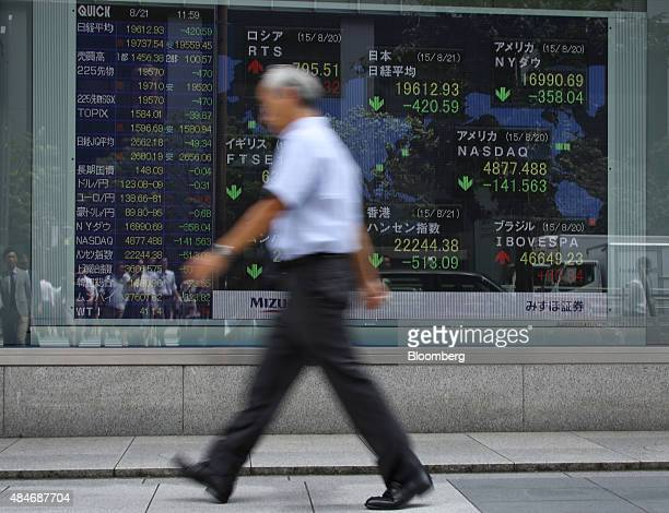 A pedestrian walks past an electronic board outside a securities firm in Tokyo Japan on Friday Aug 21 2015Japanese stocks plunged with the Topix...