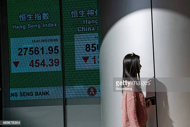 A pedestrian walks past an electronic display showing the closing figure of the Hang Seng Index at the Hang Seng Bank Ltd headquarters in Hong Kong...