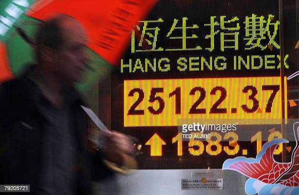 A pedestrian walks past an electronic Hang Seng index board in Hong Kong 25 January 2008 Hong Kong share prices closed sharply higher 25 January up...