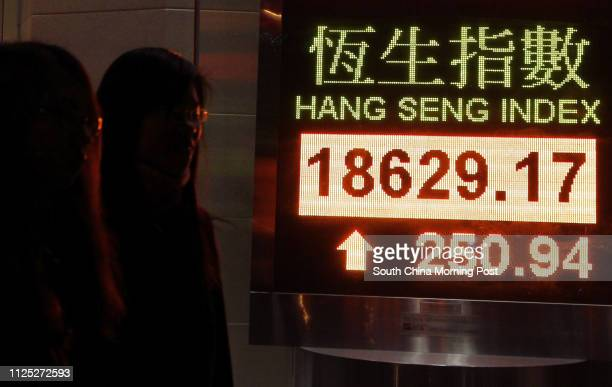A pedestrian walks past an electronic panel showing the Hang Seng Index at Wan Chai Dec 23 2011 Hong Kong's Hang Seng Index increased by 25094 points...