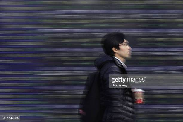 A pedestrian walks past an electronic stock board at a securities firm in Tokyo Japan on Monday Dec 5 2016 Japanese shares fell Monday morning as the...