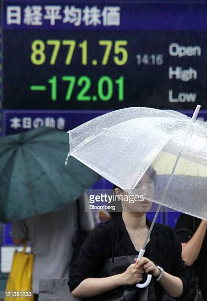 Pedestrian walks past an electronic stock board displaying a midday figure of the Nikkei 225 Stock Average outside a securities firm in Tokyo, Japan,...