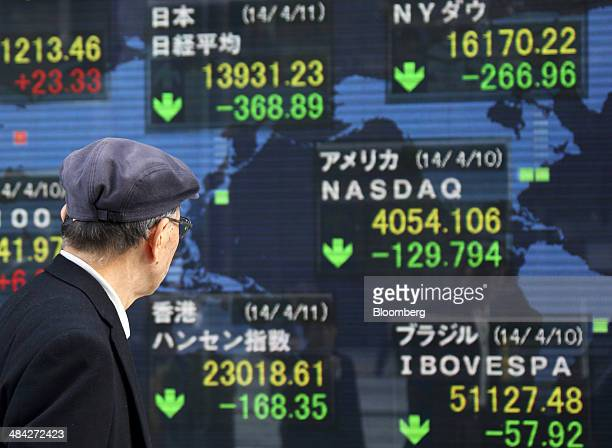 Pedestrian walks past an electronic stock board displaying a mid-day figure of the Nikkei 225 Stock Average, center top, outside a securities firm in...