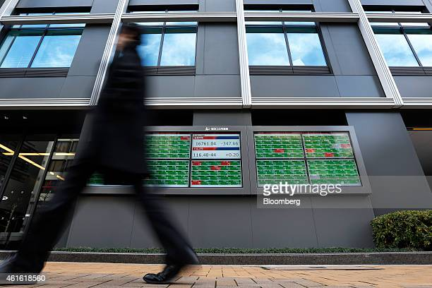 A pedestrian walks past an electronic stock board displaying the figure of the Nikkei 225 Stock Average top center and the exchange rate of the yen...