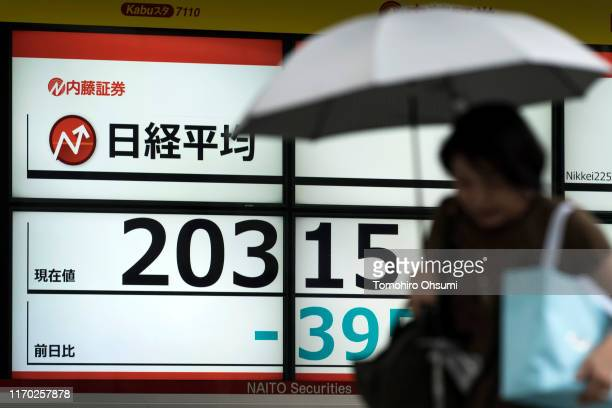 Pedestrian walks past an electronic stock board displaying the Nikkei 225 Stock Average figure on August 26, 2019 in Tokyo, Japan. Japanese stocks...