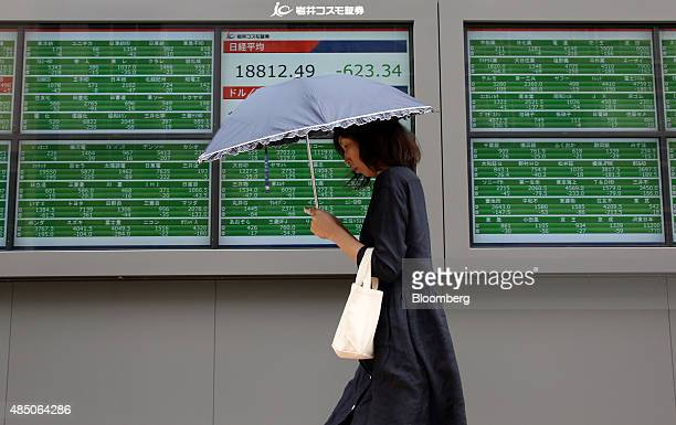 A pedestrian walks past an electronic stock board displaying the Nikkei 225 Stock Average outside a securities firm in Tokyo Japan on Monday Aug 24...