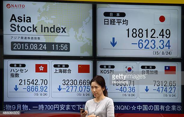 A pedestrian walks past an electronic stock board displaying the Nikkei 225 Stock Average top right the Hang Seng Index bottom left the Shanghai...
