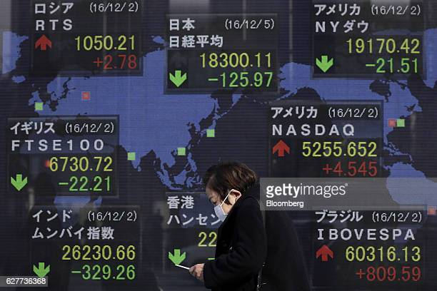 A pedestrian walks past an electronic stock board displaying the Nikkei Stock Average figure top center and other stock indices at a securities firm...