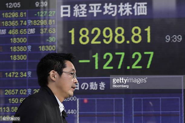 A pedestrian walks past an electronic stock board displaying the Nikkei Stock Average figure at a securities firm in Tokyo Japan on Monday Dec 5 2016...