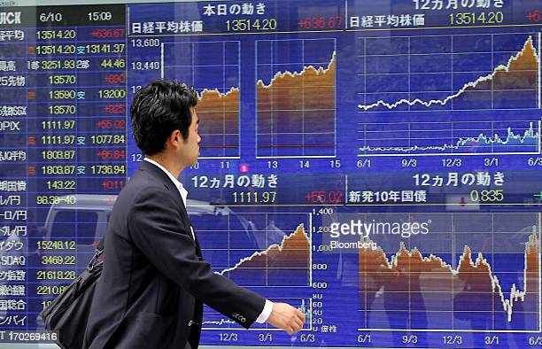 A pedestrian walks past an electronic stock board in Tokyo Japan on Monday June 10 2013 Asian stocks climbed led by the biggest gain in Japans Topix...
