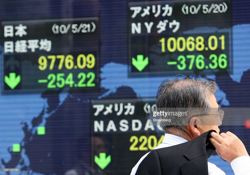 A pedestrian walks past an electronic stock board outside a securities firm in Tokyo, Japan, on Friday, May 21, 2010. Japanese stocks fell, putting key indexes on course for their biggest weekly drops in more than a year, as rising U.S. unemployment and a deepening split in Europe spurred concern the global economic recovery will stall. Photographer: Tomohiro Ohsumi/Bloomberg via Getty Images