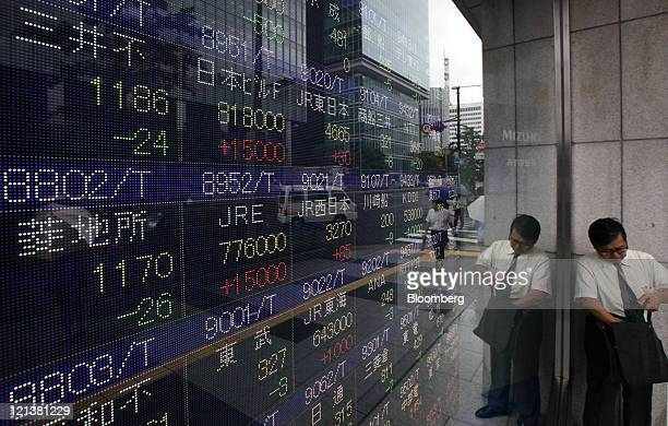 Pedestrian walks past an electronic stock board outside a securities firm in Tokyo, Japan, on Friday, Aug. 19, 2011. Japanese stocks fell for a third...