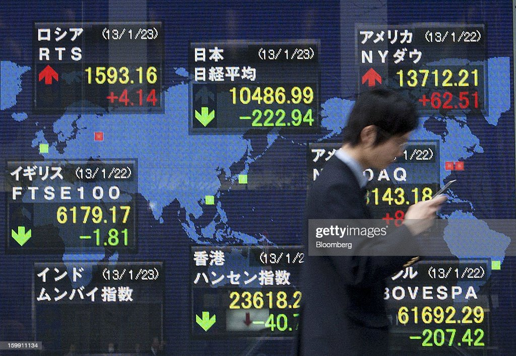 A pedestrian walks past an electronic stock board outside a securities firm in Tokyo, Japan, on Wednesday, Jan. 23, 2013. Japan shares declined, with the Nikkei 225 Stock Average posting its first three-day decline since elections were called, as the yen climbed after the Bank of Japan said it will wait a year to add open-ended stimulus. Photographer: Tomohiro Ohsumi/Bloomberg via Getty Images