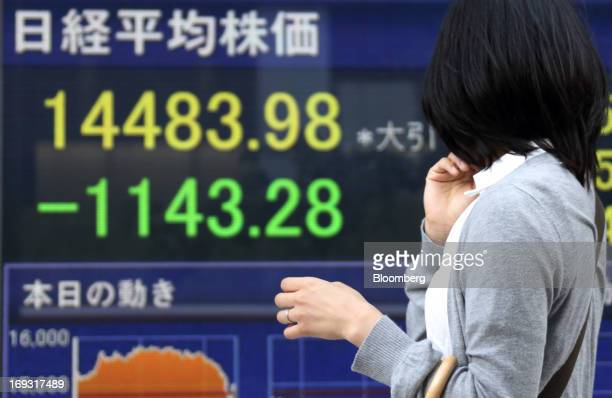A pedestrian walks past an electronic stock board showing the closing figure of the Nikkei 225 Stock Average outside a securities firm in Tokyo Japan...