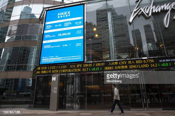 A pedestrian walks past an electronic ticker board and a screen displaying stock figures outside the Exchange Square complex which houses the Hong...
