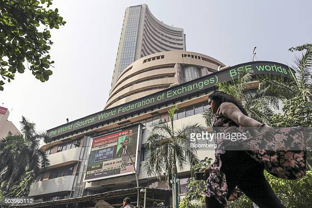 A pedestrian walks past an electronic ticker board that indicates stock figures at the Bombay Stock Exchange in Mumbai India on Friday Jan 8 2016...