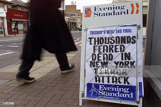 Pedestrian walks past an evening newspaper billboard whose headline reports the terrorist attacks on the United States September 11, 2001 in London.