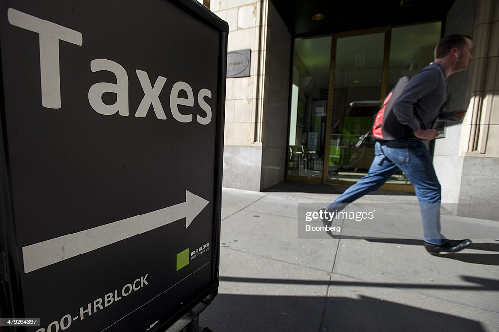 A pedestrian walks past an H&R Block, Inc. office in San Francisco, California, U.S., on Friday, March 14, 2014. The deadline for filing 2013 U.S. taxes is April 15. Photographer: David Paul Morris/Bloomberg via Getty Images