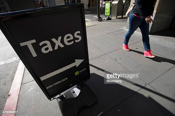 A pedestrian walks past an HR Block Inc office in San Francisco California US on Friday March 14 2014 The deadline for filing 2013 US taxes is April...