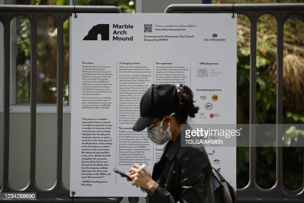 Pedestrian walks past an information board at the Marble Arch Mound, a new temporary attraction, next to Marble Arch in central London on July 28,...