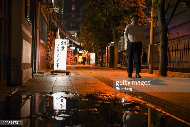 Pedestrian walks past an izakaya restaurant built under railway tracks in Tokyo, Japan, on Tuesday, Sept. 8, 2020. In Tokyo, the spaces beneath...