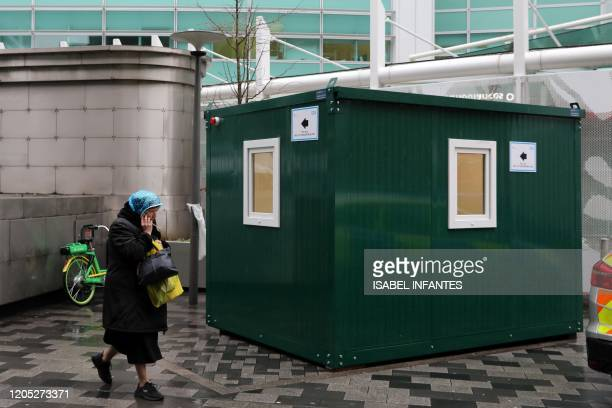 A pedestrian walks past an NHS 111 Coronavirus Pod for people who believe they may be suffering from the virus to attend and speak to doctors outside...