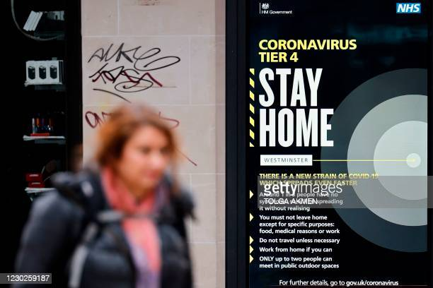 Pedestrian walks past an NHS COVID-19 information board, alerting people that London is in Tier 4 coronavirus restrictions, England's strictest...