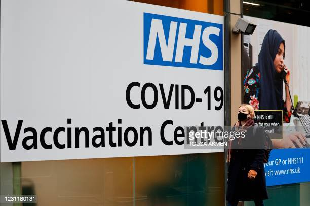 Pedestrian walks past an NHS Covid-19 vaccination centre in Westfield Stratford City shopping centre in east London on February 15, 2021 as Britain's...